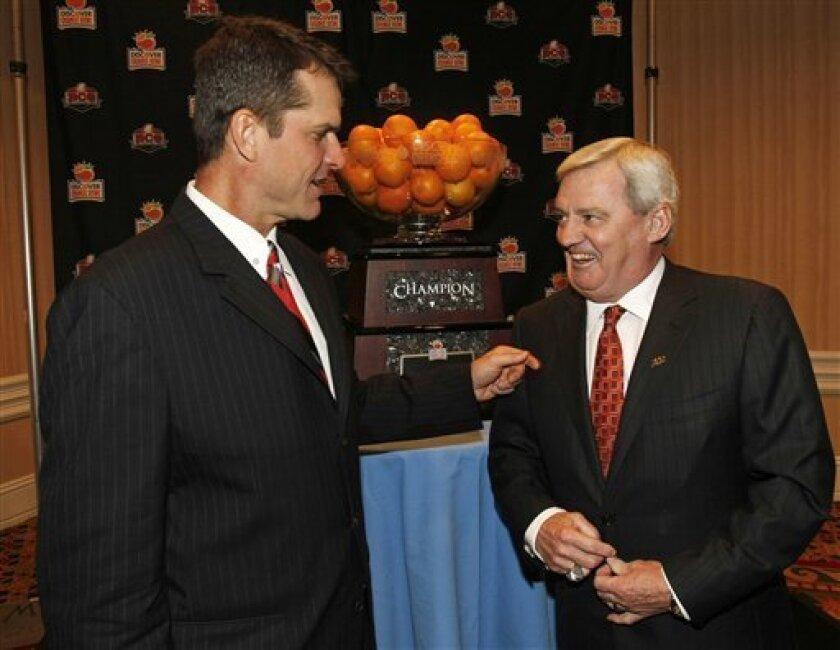 Stanford football head coach Jim Harbaugh, left, and Virginia Tech head coach Frank Beamer joke before posing for a photo with the Orange Bowl during a coach's news conference in Ft. Lauderdale, Fla., Sunday, Jan. 2, 2011. Virginia Tech plays Stanford in the Orange Bowl NCAA college football game on Jan. 3, 2010. (AP Photo/Hans Deryk)