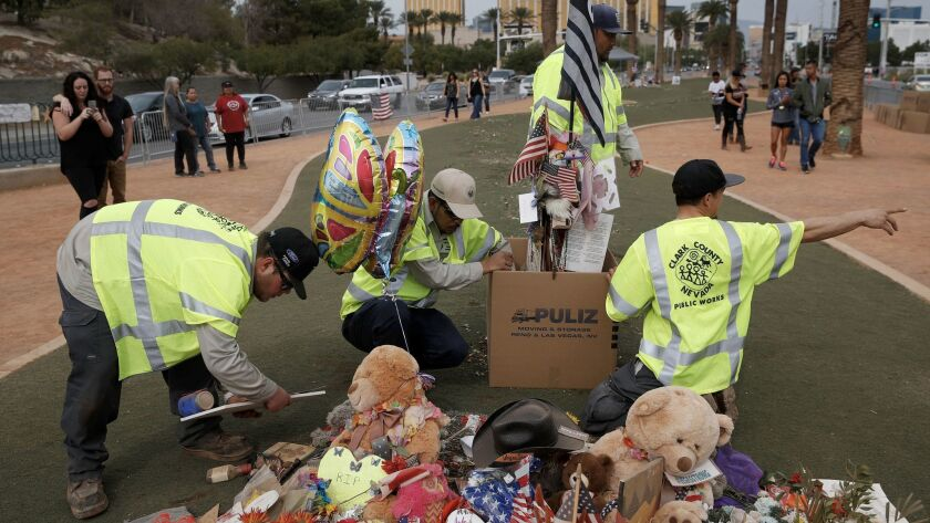 People look on as workers remove a makeshift memorial honoring the victims of the Oct. 1 mass shooti