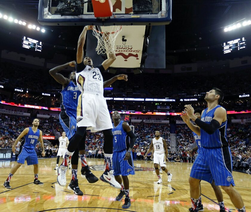 New Orleans Pelicans forward Anthony Davis (23) goes to the basket in front of Orlando Magic center Dewayne Dedmon (3) in the first half of an NBA basketball game in New Orleans, Tuesday, Nov. 3, 2015. (AP Photo/Gerald Herbert)
