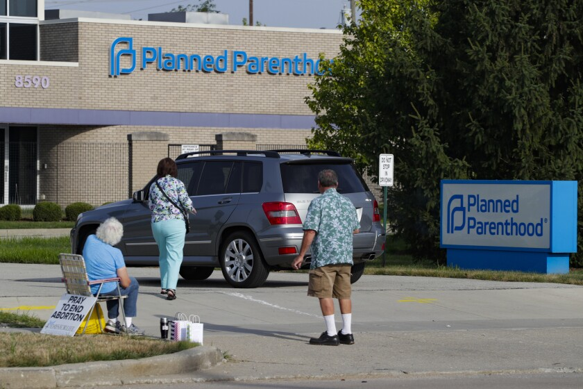 FILE - In this Aug. 16, 2019 file photo, abortion protesters attempt to handout literature as they stand in the driveway of a Planned Parenthood clinic in Indianapolis. A federal judge has blocked a new Indiana law that would require doctors to tell women undergoing drug-induced abortions about a disputed treatment for potentially stopping the abortion process. The ruling Wednesday, June 30, 2021, came just before the so-called abortion reversal law adopted by Indiana's Republican-dominated Legislature was to take effect Thursday. (AP Photo/Michael Conroy)