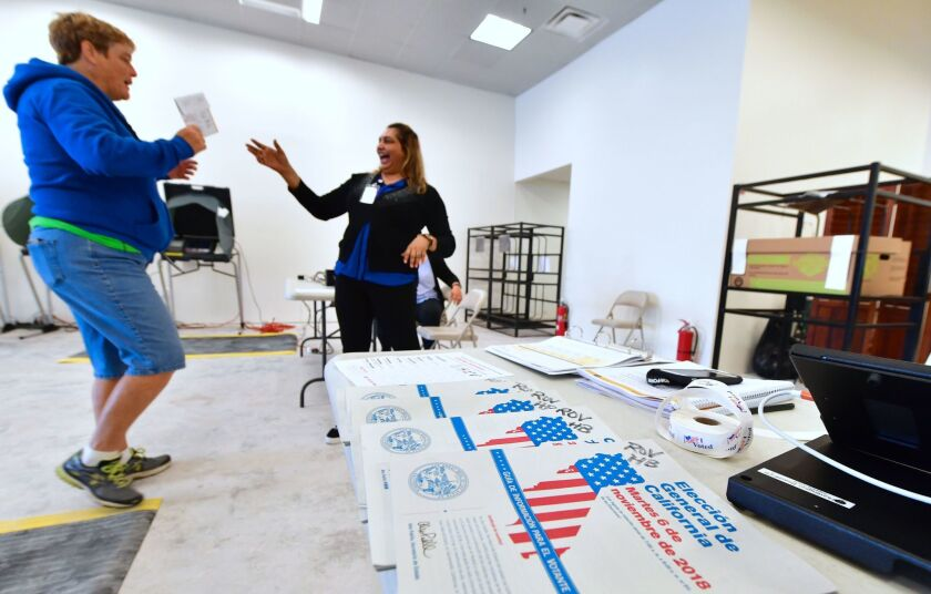 Ballots are dropped off at an Early Vote Center in Huntington Beach on Oct. 27 as voting begins in Orange County.