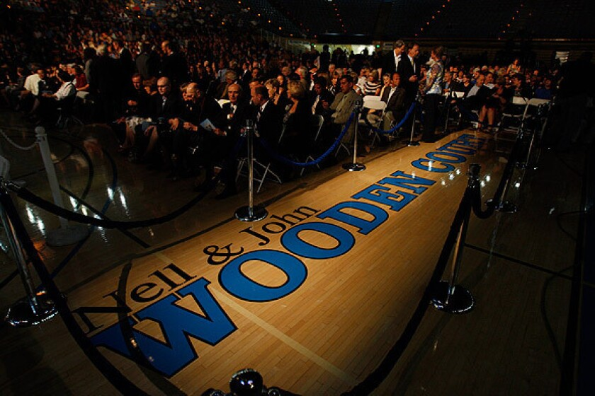 A spotlight shines on the new name for the Pauley Pavilion basketball court at UCLA during the memorial service for the legendary coach.