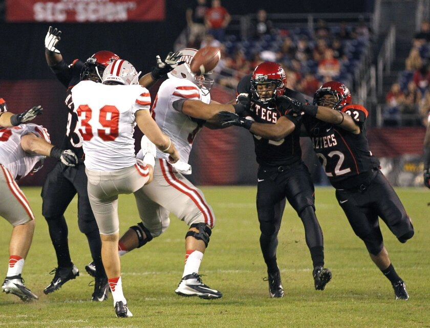 Aztecs special teams blocks UNLV's Chase Lansford's punt as the Aztecs played UNLV in football Saturday night at Qualcomm Stadium in San Diego.