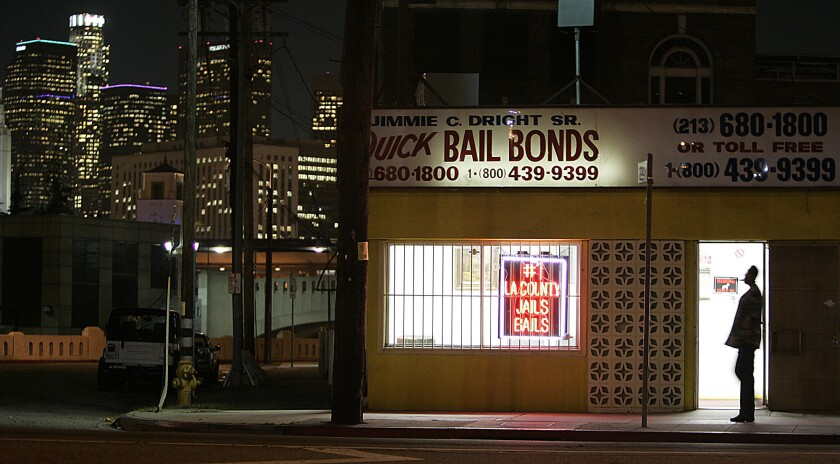 The lights of downtown Los Angeles shine behind bail bond row on Vignes Street.