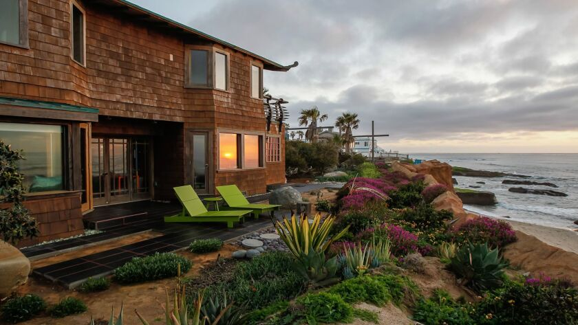 A sunset view of the 1913 Sunset Cliffs bungalow that recently underwent a major renovation.