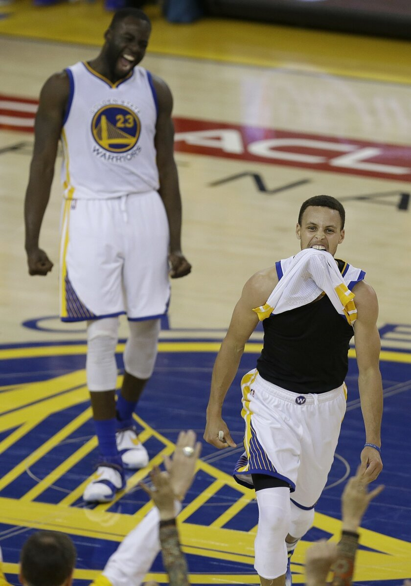 Golden State Warriors guard Stephen Curry, right, and Draymond Green celebrate after beating the Oklahoma City Thunder in Game 7 of the NBA basketball Western Conference finals in Oakland, Calif., Monday, May 30, 2016. The Warriors won 96-88. (AP Photo/Ben Margot)