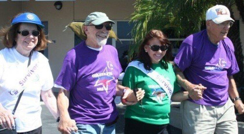 Cancer survivors walk the track hand-in-hand. Photo/Kristina Houck