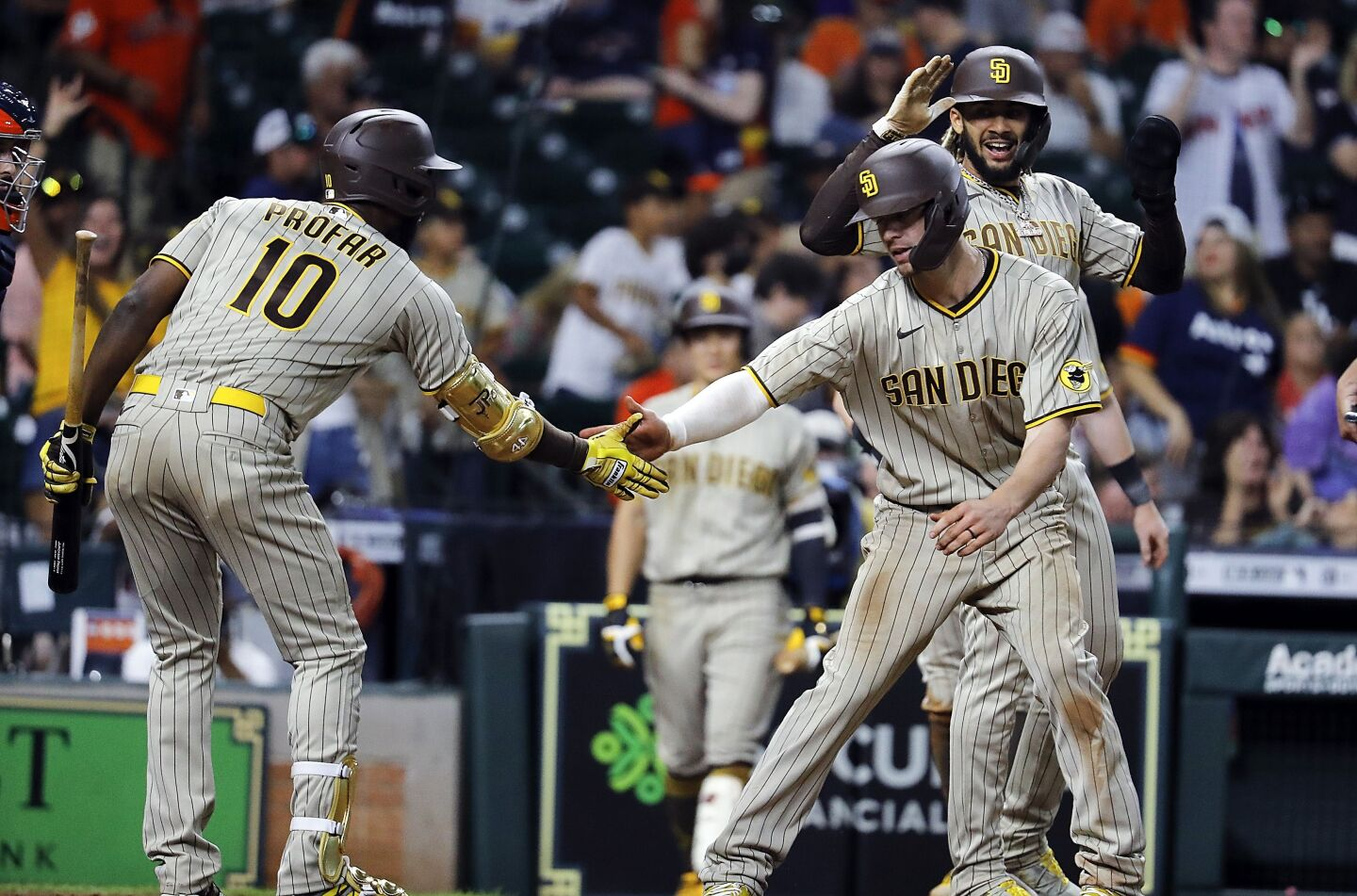 HOUSTON, TEXAS - MAY 29: Wil Myers #5 of the San Diego Padres is congratulated by Jurickson Profar #10 and Fernando Tatis Jr. #23 after hitting a three-run home run in the twelfth inning against the Houston Astros at Minute Maid Park on May 29, 2021 in Houston, Texas. (Photo by Bob Levey/Getty Images)