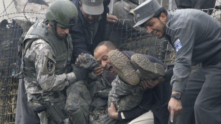 An injured U.S. soldier is helped getting out following a blast in Kabul, Afghanistan, Saturday, Jan