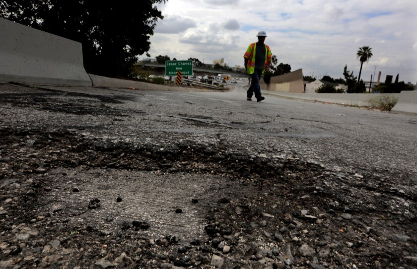 A Caltrans maintenance supervisor walks along a portion of a southbound 5 Freeway onramp where potholes and cracks are common on June 5, 2015.