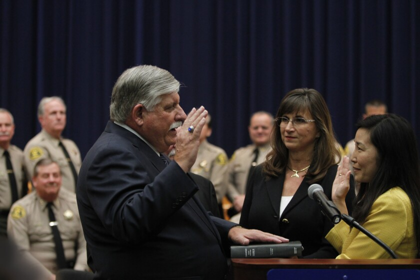 Sachi Hamai, right, then-executive officer to the Los Angeles Board of Supervisors, administers the oath of office to interim Sheriff John Scott on Jan. 30, 2014. Hamai is now the county's interim chief executive officer and Scott has been replaced by Sheriff Jim McDonnell.