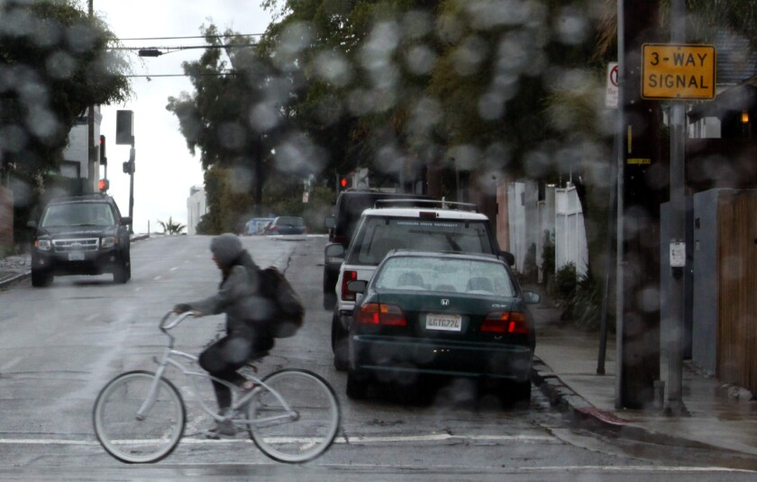 A bicyclist makes her way along Main Street during Tuesday morning rain in Venice.