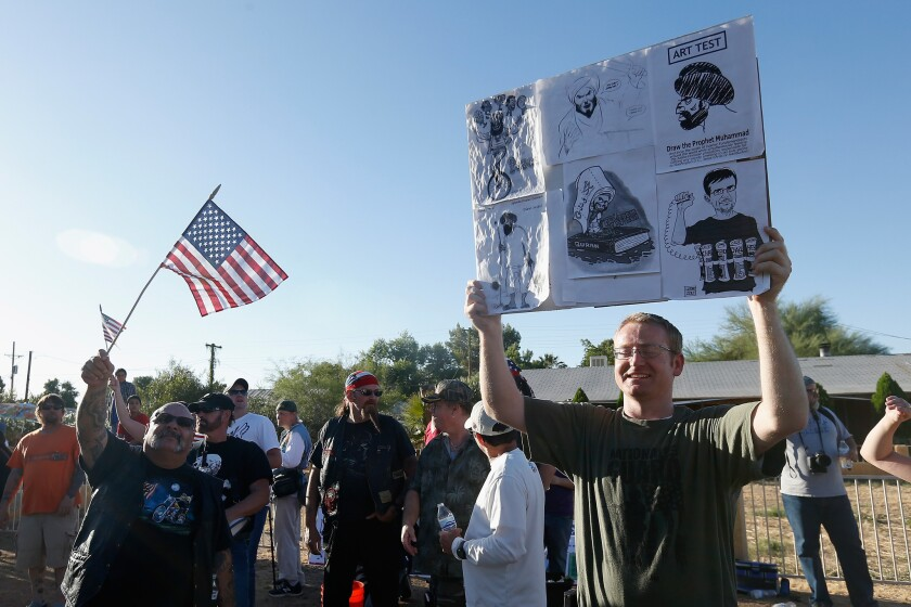 Demonstrators hold up signs depicting the prophet Muhammad as they stage an anti-Islam protest outside a mosque in Phoenix.