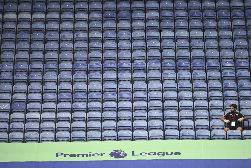 A steward wearing a face mask sits on empty stands during the English Premier League soccer match between Leicester City and Manchester United at the King Power Stadium, in Leicester, England, Sunday, July 26, 2020. (Oli Scarff/Pool via AP)