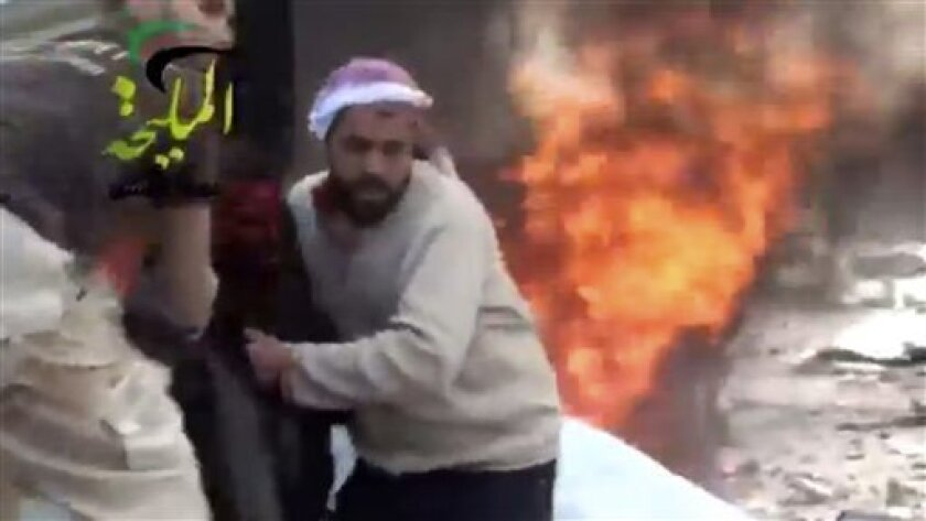 This citizen journalism image taken from video provided by Shaam News Network, which has been authenticated based on its contents and other AP reporting, shows a wounded man being pulled from the site of a Syrian government airstrike on a gas station in the eastern Damascus suburb of Mleiha, Syria,