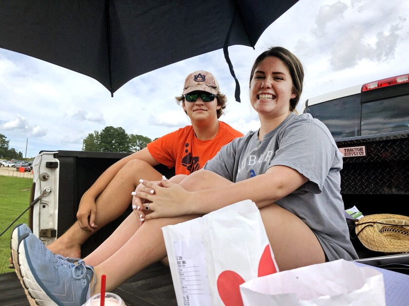 Lily Moreman, right, secures a prime tailgating spot Friday with her friend, Rylan Mayberry.