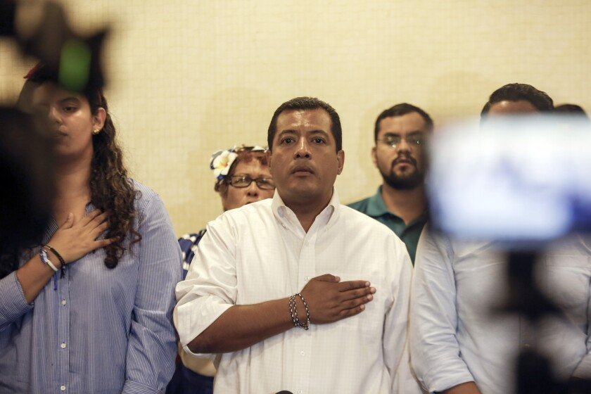 Nicaraguan opposition activist Felix Maradiaga, center, stands at attention as the national anthem is sung during a press conference in Managua, Nicaragua, Wednesday, Sept. 18, 2019. Maradiaga who was accused of terrorism by the government of President Daniel Ortega, returned on Monday to Nicaragua from self-imposed exile and said that he will not abandon his country ever again. (AP Photo/Alfredo Zuniga)