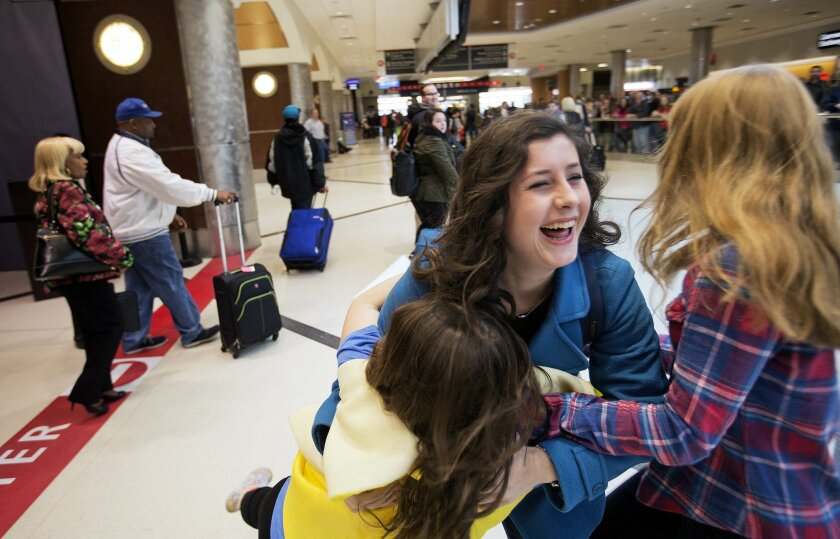 Ginny Barr, 18, center, is swarmed by her sisters Sarah,15, left, and Molly, 13, as she arrives at Hartsfield–Jackson Atlanta International Airport from college in North Carolina to spend Thanksgiving at home in Fort Benning, Ga., Wednesday, Nov. 25, 2015, in Atlanta. The big Thanksgiving getaway went into full swing Wednesday with drivers delighted by the lowest November gas prices in years and many airline passengers undaunted by terrorism fears and long lines at security checkpoints. (AP Photo/David Goldman)