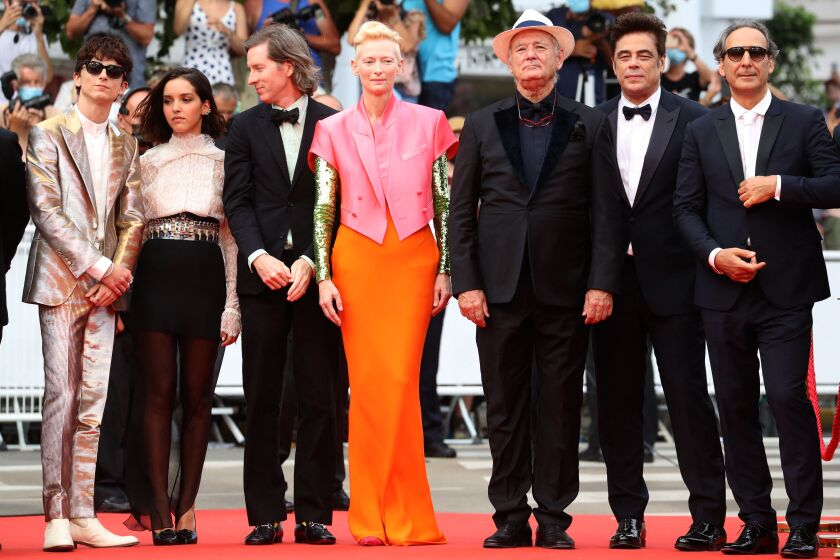 Seven people dressed in formalwear stand on a red carpet