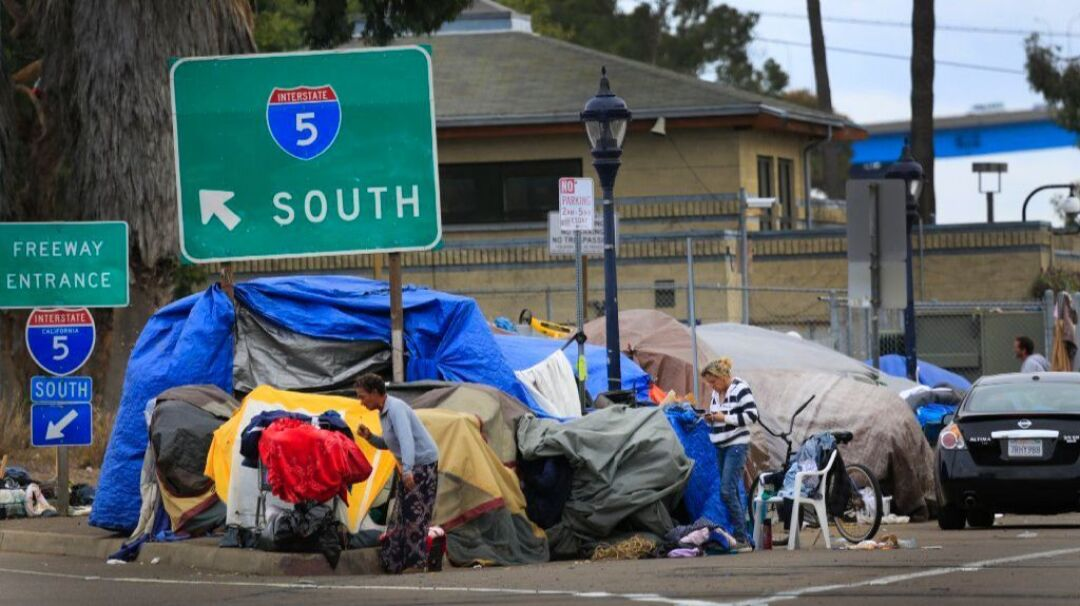 Tents housing the homeless line an on-ramp to Interstate 5.