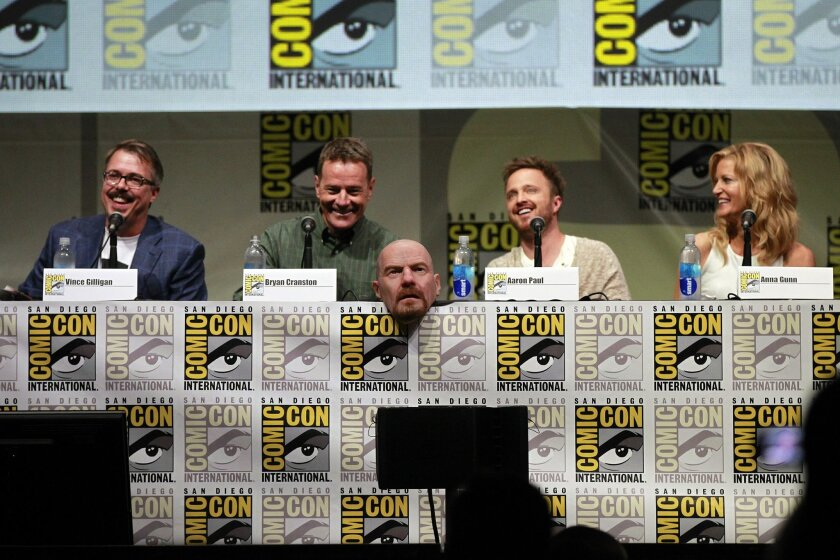 Vince Gilligan, left, Executive Producer of the television show Breaking and actors Bryan Cranston, Aaron Paul, and Anna Gunn speak at Hall H at Comic-Con. A mask from the character Walter White sits on the table.