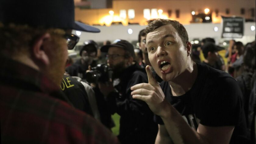 Ian Jameson, of Pasadenans and Altadenans Against Police Violence, shouts at a Trump supporter during a protest against President Trump, who was attending a private event in Beverly Hills .