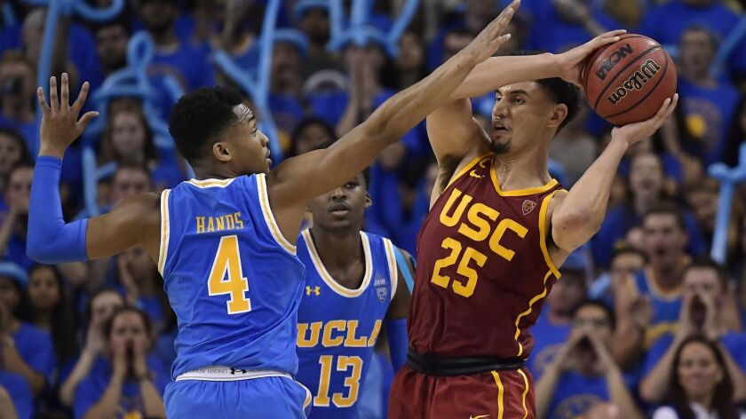 USC forward Bennie Boatwright, right, tries to pass as UCLA guard Jaylen Hands defends during the second half on Thursday. UCLA won 93-88 in overtime.