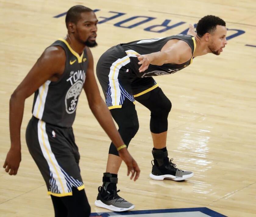 Los jugadores de los Golden State Warriors Stephen Curry (dcha) y Kevin Durant (izda) en acción durante un partido de la NBA. EFE/Archivo