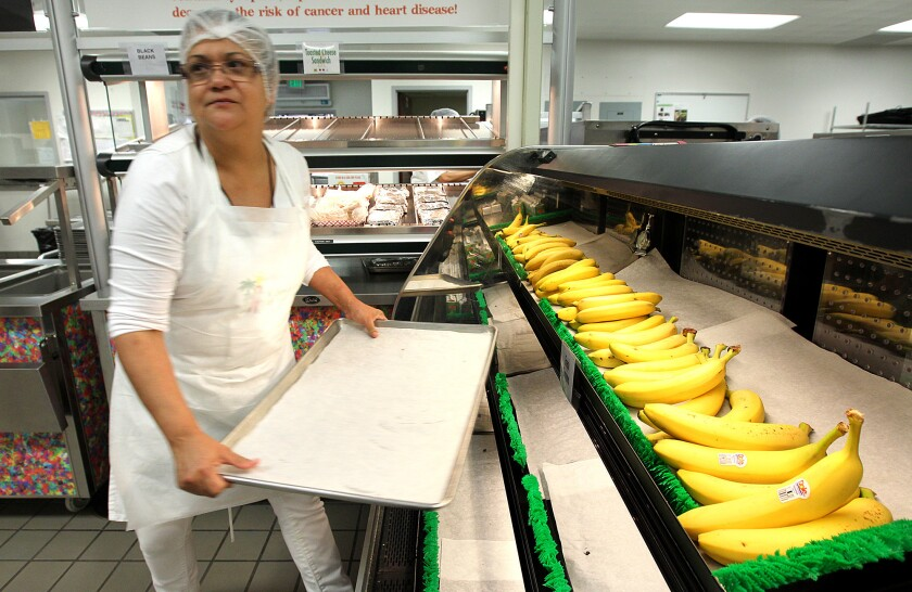 Kitchen worker Linda Gomez stocks bananas in a display case inside the cafeteria during lunch time at Bravo Medical Magnet High School in Los Angeles