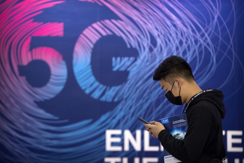Un hombre mira su teléfono al pasar frente a un cartel publicitario de servicios de G% en la PT Expo, Beijing