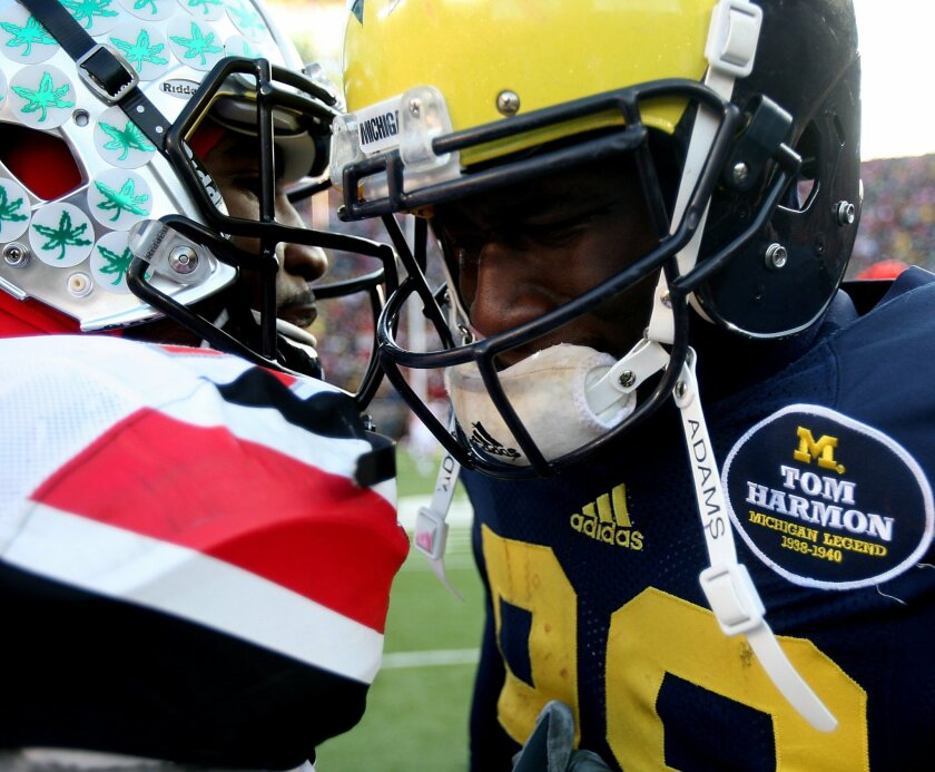 Michigans' Devin Gardner is comforted by Ohio States' Braxton Miller after Michigan's 42-41 loss in an NCAA college football game Saturday, Nov. 30, 2013 at Michigan Stadium in Ann Arbor, Mich. (AP Photo/Detroit Free Press, Kirthmon F. Dozier) DETROIT NEWS OUT; NO SALES, MANDATORY CREDIT