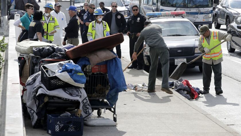 Los Angeles sanitation workers perform a cleanup this month near the new El Puente shelter in the El Pueblo historic district as police escorts watch.