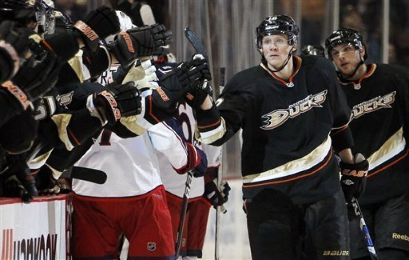 Anaheim Ducks right wing Corey Perry (10) celebrates with teammates after scoring against the Columbus Blue Jackets during the first period of an NHL hockey game in Anaheim, Calif., Sunday, Jan. 8, 2012. (AP Photo/Alex Gallardo)