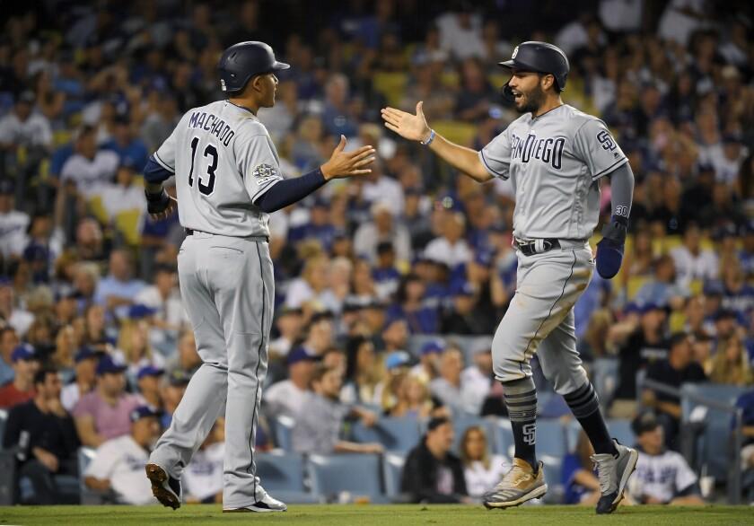 El jugador de los Padres de San Diego Eric Hosmer (derecha) recibe la felicitación de su compañero Manny Machado al anotar en un doble de Josh Naylor en el sexto inning del juego de la MLB que enfrentó a su equipo con los Dodgers de Los Ángeles, el 2 de agosto de 2019, en Los Ángeles. (AP Foto/Mark J. Terrill) ** Usable by HOY, ELSENT and SD Only **