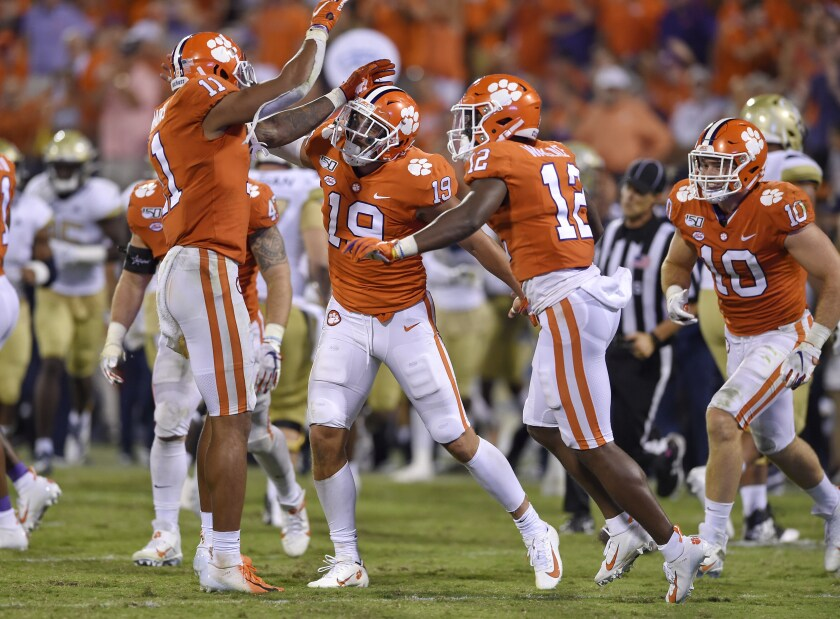 Clemson's Tanner Muse, center, Isaiah Simmons, left, and K'Von Wallace celebrate Muse's interception during the second half against Georgia Tech on Thursdayin Clemson, S.C. Clemson won 52-14.