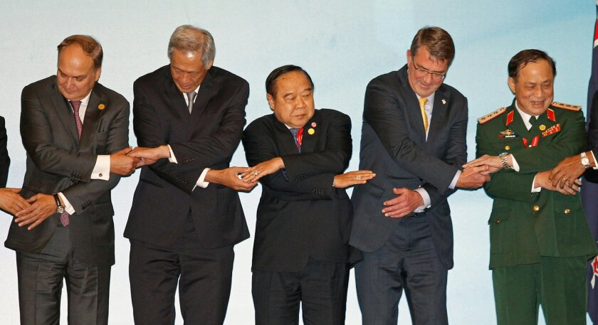 From left, Russia's Deputy Defense Minister Anatoly Antonov, Singapore's Defense Minister Ng Eng Hen, Thailand's Defense Minister Gen. Prawit Wongsuwon, U.S. Defense Secretary Ash Carter and Vietnam's Deputy Defense Minister Nguyen Van Hien joint hands as they pose for photographers after the Assoc
