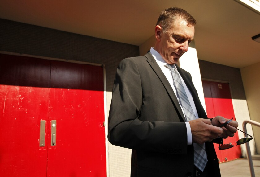 Los Angeles Unified School District Supt. John E. Deasy, texting before making his annual address to administrators last year. His district is one of many fighting a new financial proposal from Gov. Jerry Brown that would limit budget reserve funds.