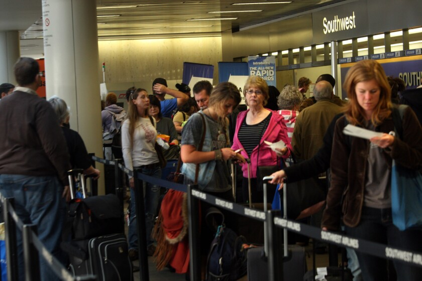 Thanksgiving travelers wait in line to check in at Los Angeles International Airport in 2011.