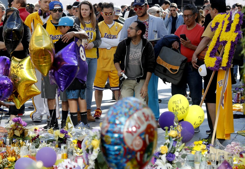Fans, several in Lakers jerseys, gather in front of balloons, flowers and other items in honor of Kobe Bryant.