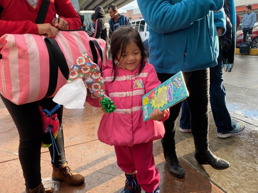 Sofia Nhanelii, 4, from Oaxaca, Mexico, opens a coloring book on Christmas Eve while her family waits for their turn to make an asylum claim. A group of volunteers known as PBJTJ handed out presents to children stuck at the border on Tuesday.