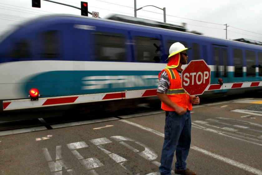 North County Transit District maintenance worker Vince Bick holds a stop sign at Enterprise Street in Escondido as a Sprinter train makes a test run between the Escondido Transit Center and Woodland Parkway in San Marcos on April 7. The agency is testing newly installed brake rotors. Photo by Don Boomer/UT San Diego