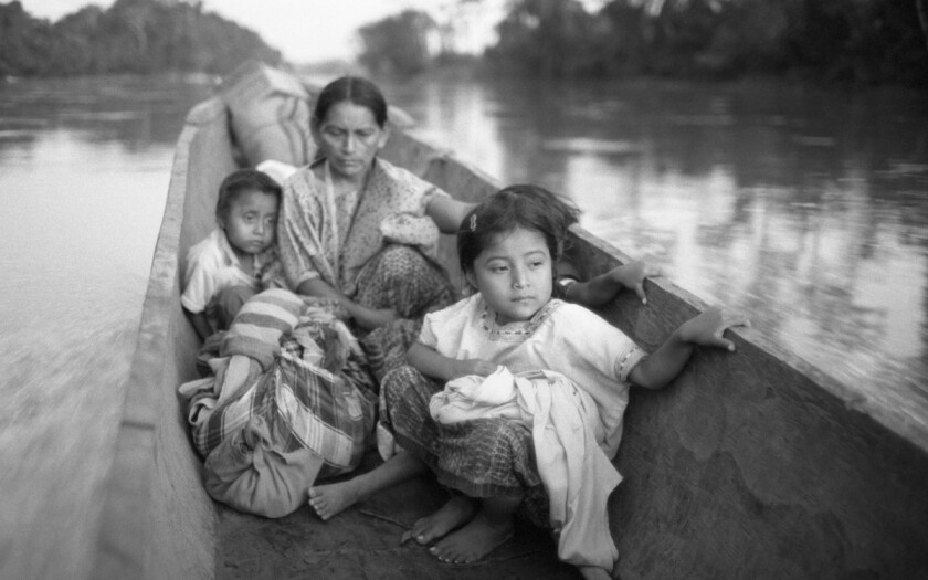 """Refugee woman and three children in a canoe, Chiapas,"" 1983, by Richard Cross, on view at L.A.'s Museum of Social Justice."