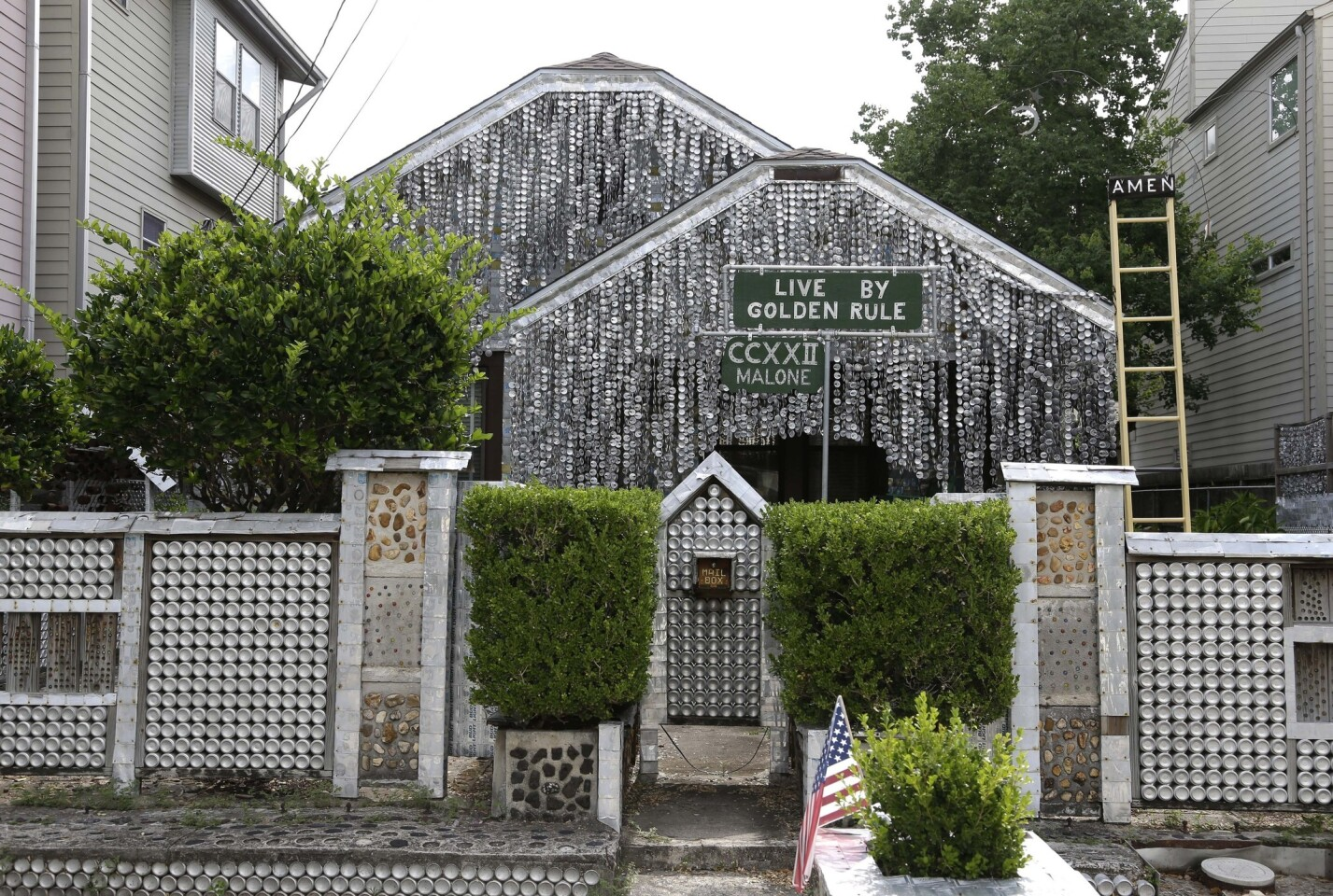 The Beer Can House, a Houston landmark, sits between newer homes.
