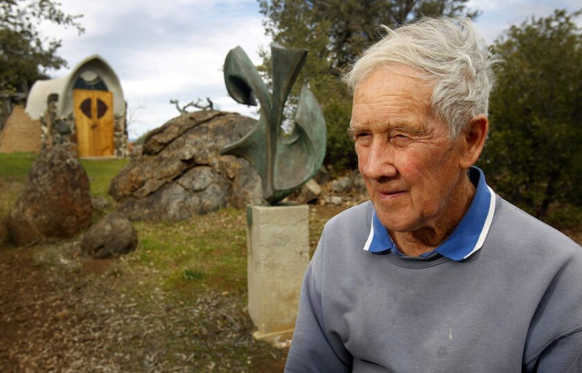 James T. Hubbell has worked in Santa Ysabel since 1958. Behind him are a bronze sculpture and one of many structures on his property.