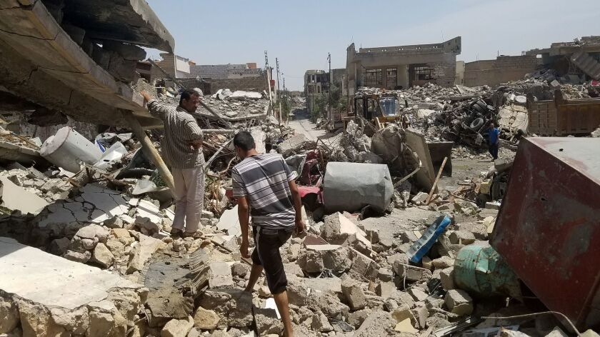 Residents of west Mosul's Jadidah neighborhood remove debris after an airstrike in March 2017.