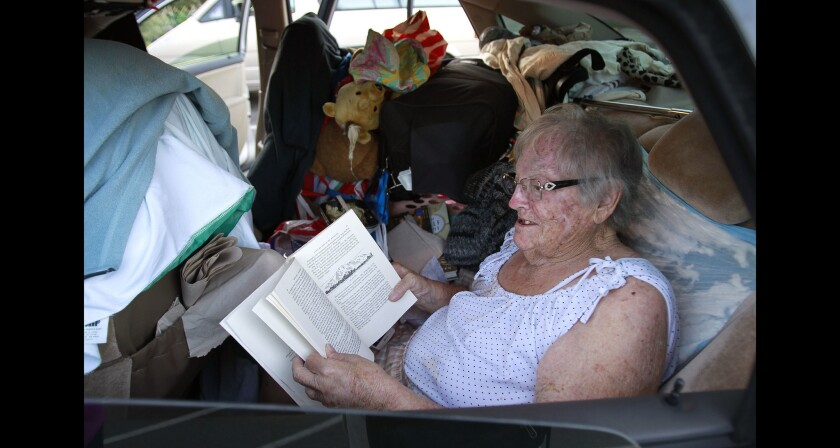 Fleur Stark reads a book while in the backseat of the car that she, her son and daughter-in-law are going to spend the night in this file photo taken in San Diego.