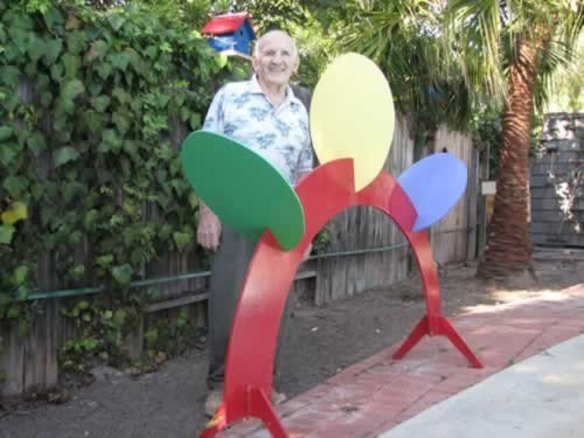 Ed Hujsak with his sculpture, 'Rainbow Arc.' Ashley Mackin