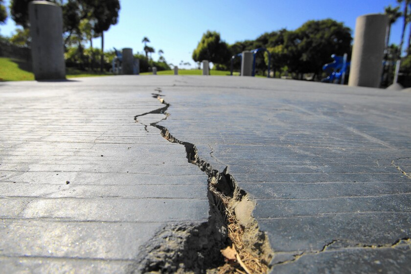 A long crack splits the sidewalk at 6.6-acre Discovery Well Park in Huntington Beach, located atop the Newport-Inglewood fault. Officials knew the fault would be an issue when they began drawing up plans that would bring thousands of new residents to the city.