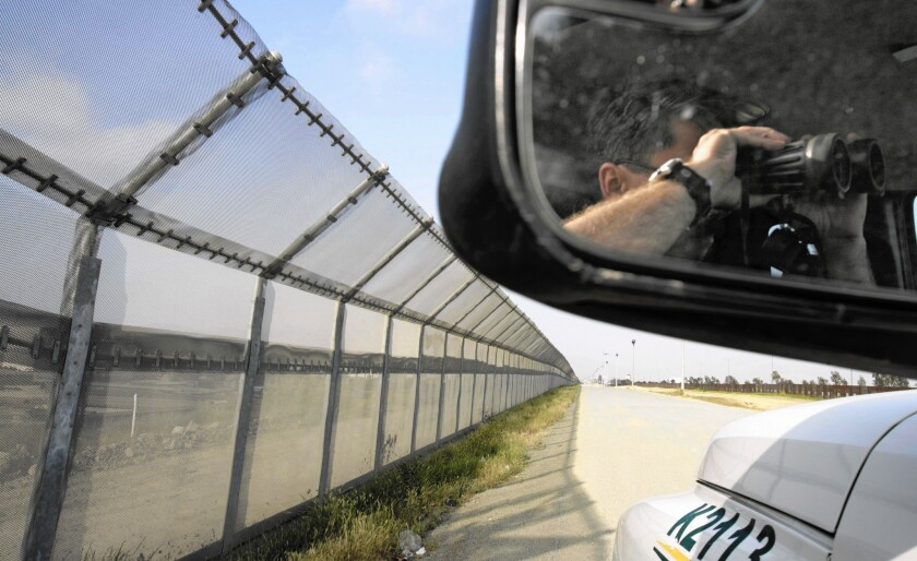 A border agent keeps watch on the Otay Mesa area. Non-citizens who cross on foot through Otay Mesa will be scanned in an effort to track non-immigrant visa holders who remain in the U.S. after permits expire.