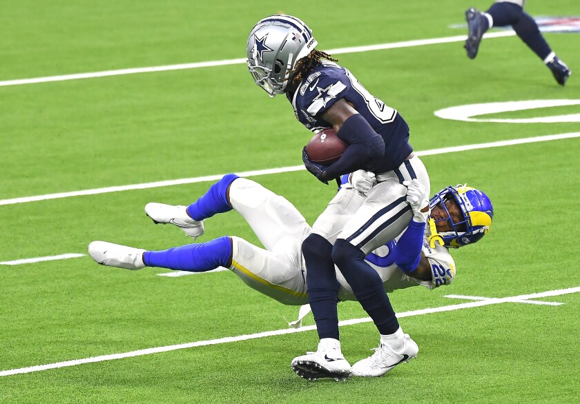 Rams corner Troy Hill tackles CeeDee Lamb after the Cowboys receiver made a catch in the second quarter.